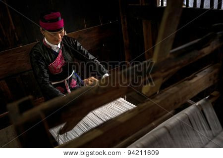 XIAPU, CHINA - JUNE 5, 2015: An unidentified lady wearing traditional costume weaves cloth from cotton strands using a traditional wooden weaving machine of several hundred years old.