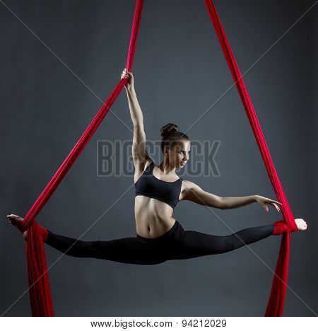 Flexible young woman dancing using hanging ribbons