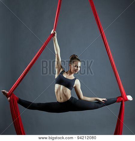 Cute dancer doing gymnastic split on aerial silks