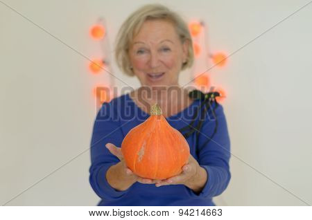 Smiling Woman Holding A Fresh Autumn Pumpkin