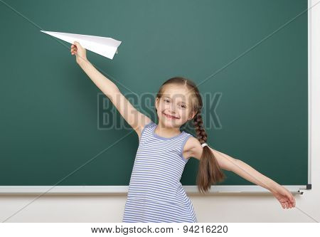 Schoolgirl with paper toy plane near school board