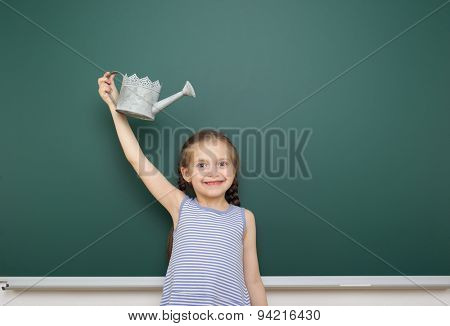 Schoolgirl with watering can near the school board