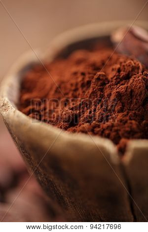 cocoa powder in spoon on roasted cocoa chocolate beans background,  focus on spoon