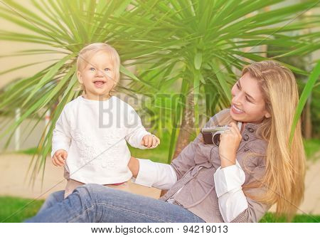 Cheerful mother taking picture of her cute little daughter in the park, happy young family having fun outdoors, parental love and enjoyment