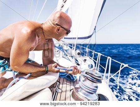 Handsome man working on sailboat, shirtless muscular captain pulling rope on winch, summer time activity, enjoying extreme water sport