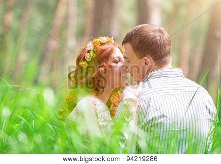 Happy loving couple kissing in the park, young lovers sitting in fresh green grass and enjoying romantic date outdoors, first affection