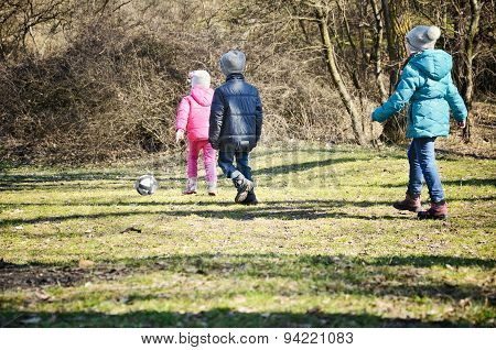 Children 6-9 Years Play With A Ball In The Park During The Cold Season