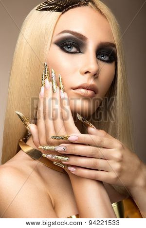 Beautiful fashionable girl in a glamorous image with bright makeup and long gold nails. Art design m