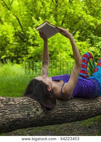 Girl Reading A Book Outdoors.