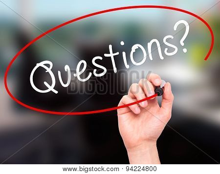 Man Hand writing Questions? with black marker on visual screen.
