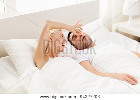 people, family, bedtime and couple concept - happy woman closing nose to her snoring man sleeping in bed at home