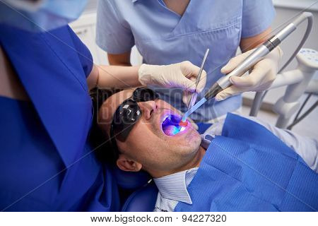 people, medicine, stomatology and health care concept - female dentist and assistant with dental curing light and mirror treating male patient teeth at dental clinic office