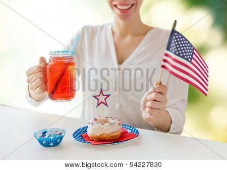 independence day celebration, patriotism and holidays concept - happy woman with donut celebrating 4th july, holding american flag and drinking juice from glass mason jar over green background
