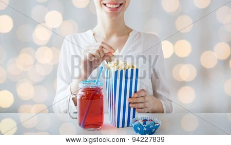 american independence day, celebration, patriotism and holidays concept - close up of woman eating popcorn with drink in glass mason jar and candies at 4th july party over lights background