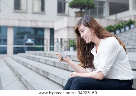 Asian female student using tablet in campus