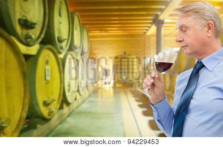 people, winery, alcohol and beverage concept - senior man smelling red wine over wine cellar background
