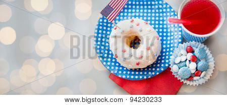 american independence day celebration, patriotism and holidays concept - close up of donut with juice and candies in disposable tableware at 4th july party from top