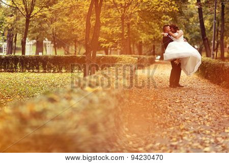 Bride And Groom Embracing In The Park