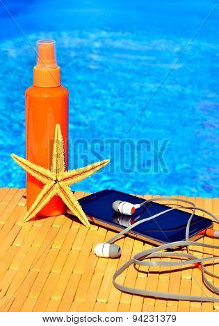Cell Phone, Sun Spray, Head Phones And Starfish Near Water