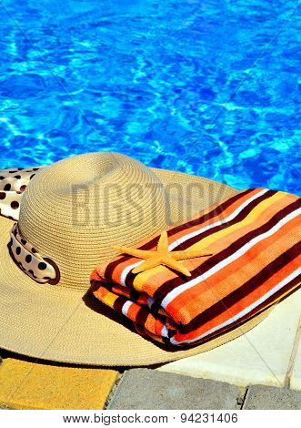 Woman Beach Hat, Bright Towel Against Blue Swimming Pool