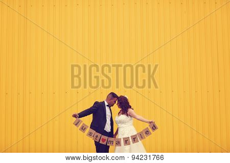 Bride And Groom Holding Just Married Sign