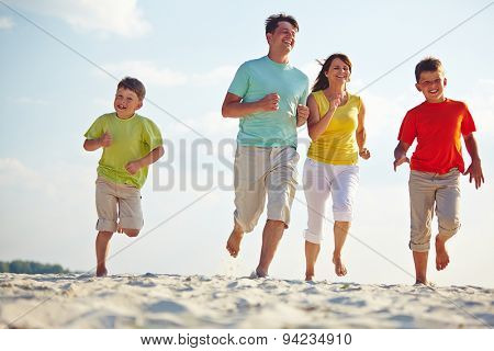 Modern family of four running on sandy beach