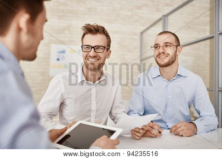 Young businessmen looking at colleague while talking at meeting