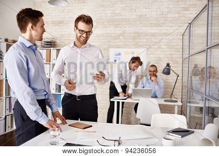 Young colleagues interacting at meeting in office