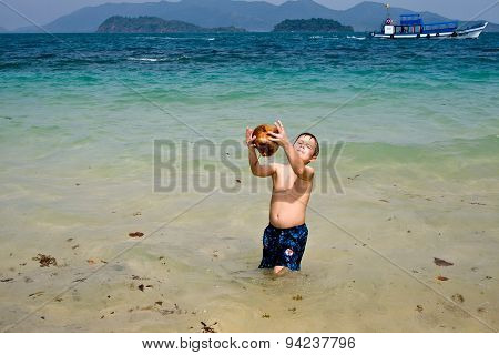 Boy Is Playing With A Coconut On A Beautiful Beach