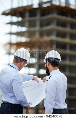 Young architects looking at blueprint with sketch of construction