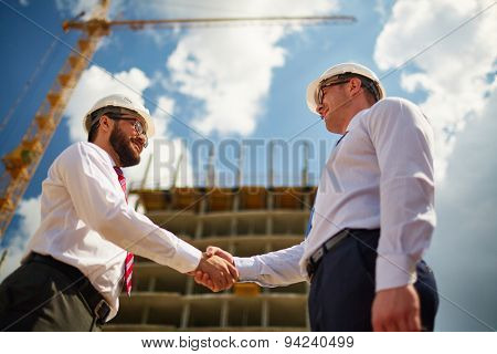 Two handsome architects making a deal outside