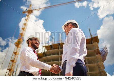 Two businessmen making agreement on background of new construction
