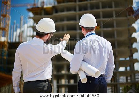 Rear view of architects looking at construction