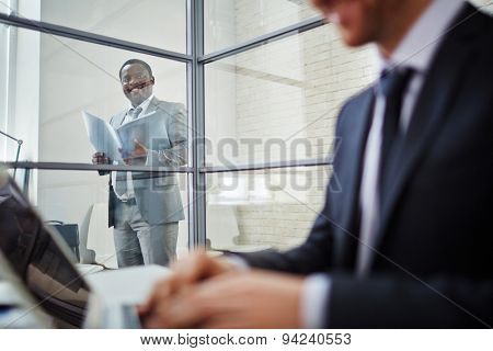 Confident businessman in suit looking at his working colleague