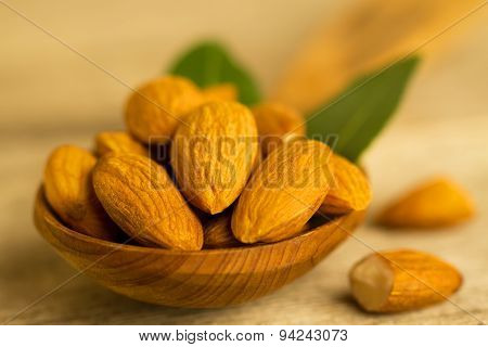 Peeled Almonds In A Spoon C Leaves On Wooden Table