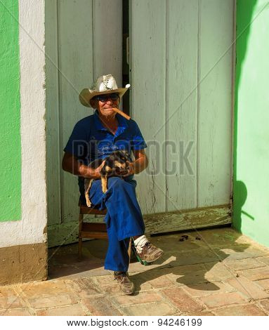 Old Cuban man with a dog and cigar in Trinidad, Cuba
