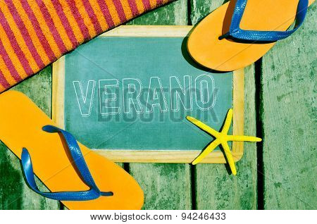 high-angle shot of a rustic wooden surface with a starfish, a beach towel, a pair of flip-flops and a chalkboard with the word verano, summer in spanish