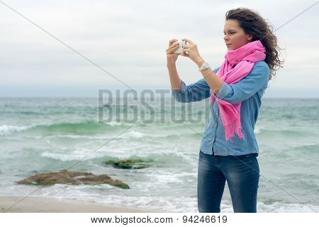 Young Woman With Curly Hair Makes The Picture Of The Seaside