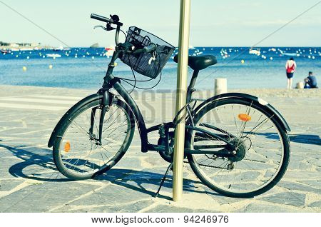 closeup of a bicycle parked in a seafront on the Mediterranean sea with blurred people on the seashore in the background, with a filter effect