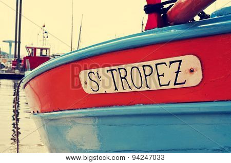closeup of the hull of a boat  moored in Saint-Tropez, France, with the text St. Tropez written in it