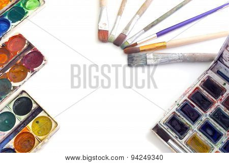 The Layout Of The Paints And Brushes On A White Background