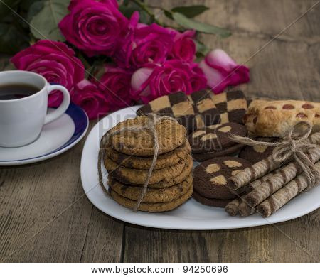 Coffee, Flowers Pink And Different Cookies On A Plate