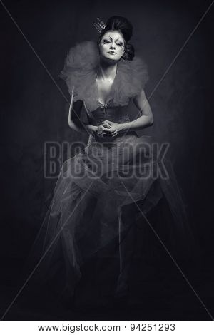 Queen. Woman With Creative Make-up In Fluffy Dress Posing Indoors. Black And White
