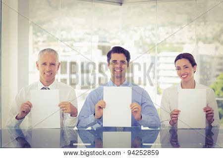 Smiling business team showing paper in the office