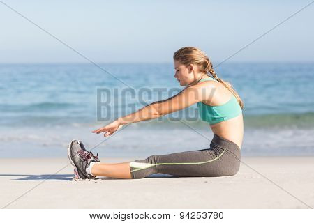 Fit woman stretching beside the sea at the beach