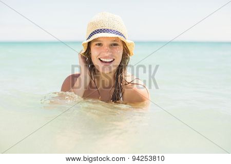 Happy pretty blonde bathing into the sea with hat at the beach