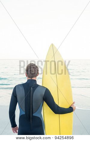 Man in wetsuit with a surfboard on a sunny day looking at sea