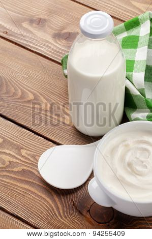 Sour cream in a bowl and milk bottle on wooden table with copy space