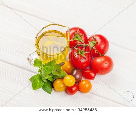 Italian food cooking ingredients. Olive oil, tomatoes, basil on wooden table