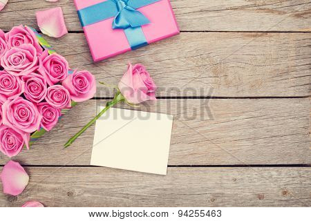 Valentines day greeting card or photo frame and gift box full of pink roses over wooden table. Top view